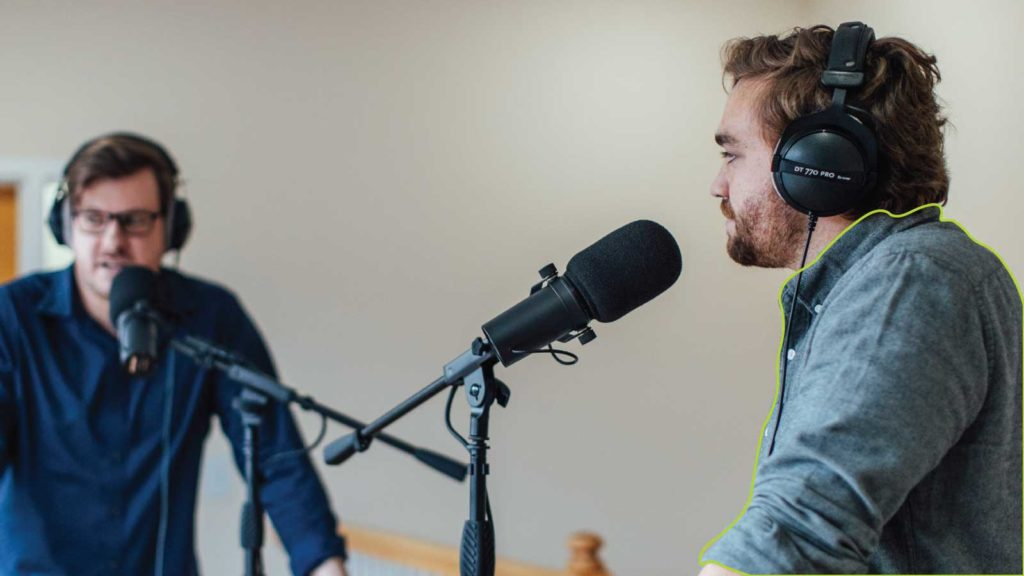 Two men recording a podcast with clothing highlighted in green