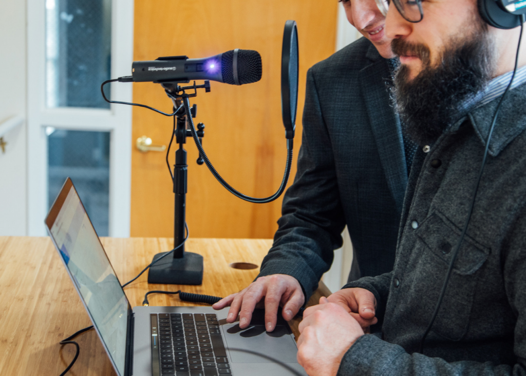 Two podcasters planning their podcast on a laptop with headphones and a microphone