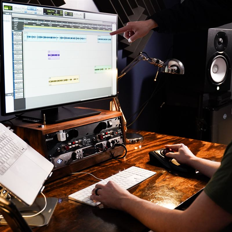 Podcast Producer working with a podcast audio engeineer pointing to a screen with ProTools