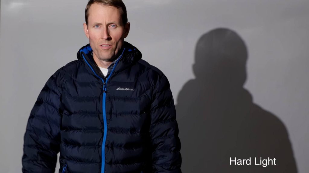 Man standing in front of gray background with a cold hard light on him