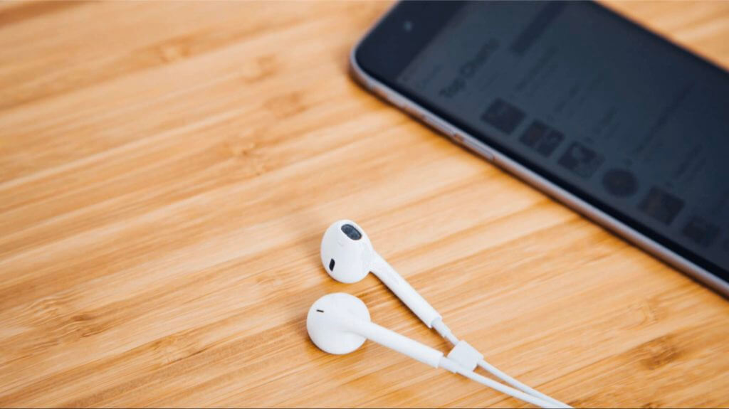 Headphones next to an iPhone with Apple Podcast Cover arts on the screen